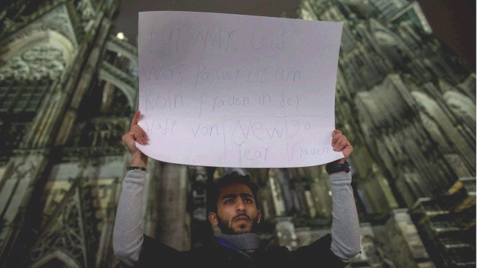 """A man hold a placard reading """"Sorry for what happened with the woman in Cologne in New Year""""s Eve, 90 women"""" outside the main station in Cologne, Germany, 06 January 2016."""