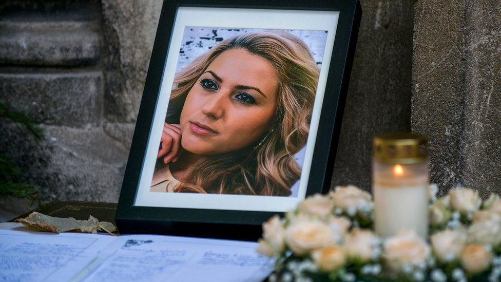 A photo frame showing a picture of Viktoria Marinova is seen laid against the stone walls of a church, with candles in tribute placed nearby