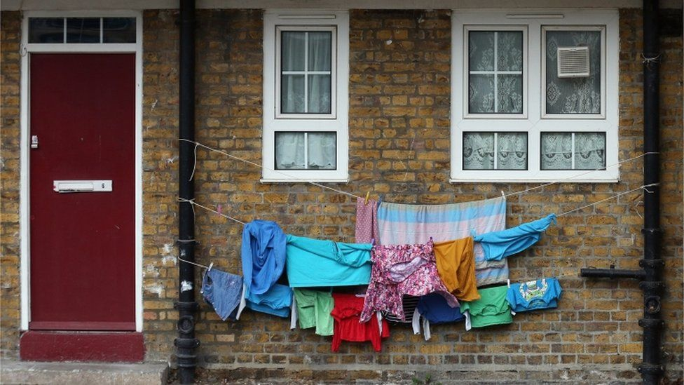 Children's clothing is hung out to dry between waste pipes in London