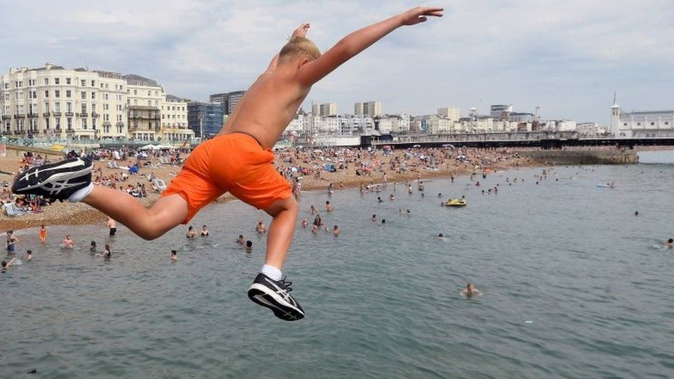 A boy jumps into the sea as he enjoys the hot weather at Brighton beach