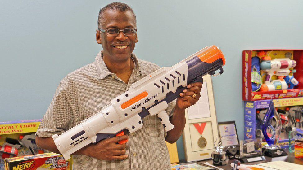 Lonnie Johnson holding some super soaker guns