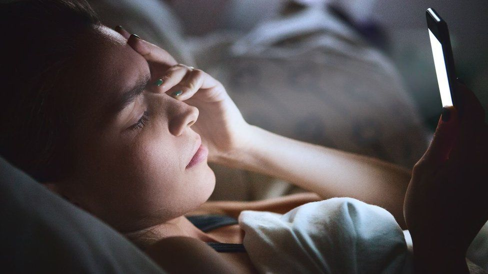 Woman in bed with smartphone