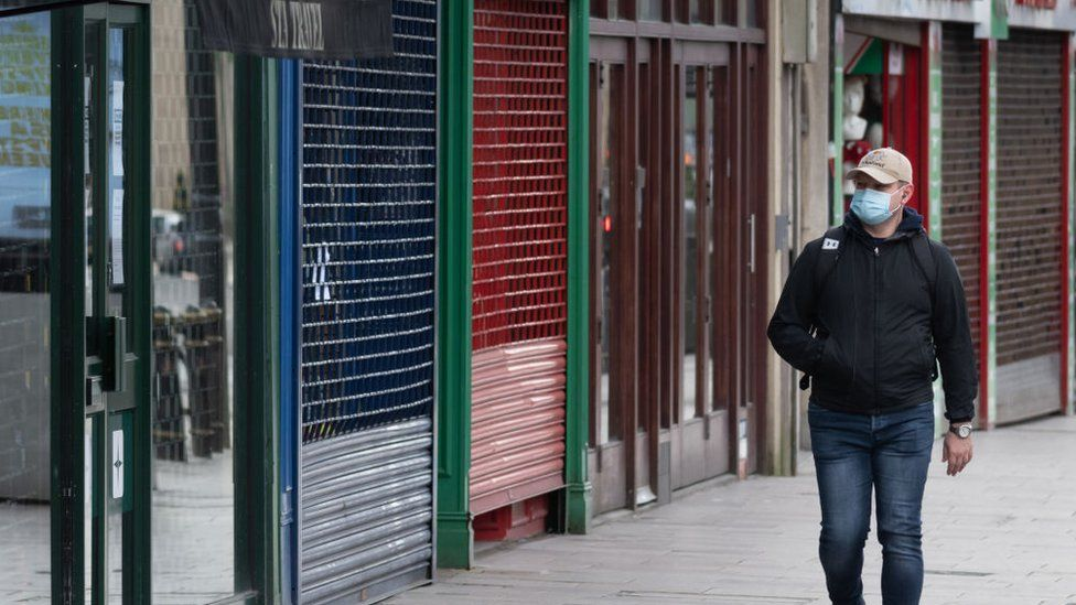 A man in a face mask walks past closed shops in Cardiff