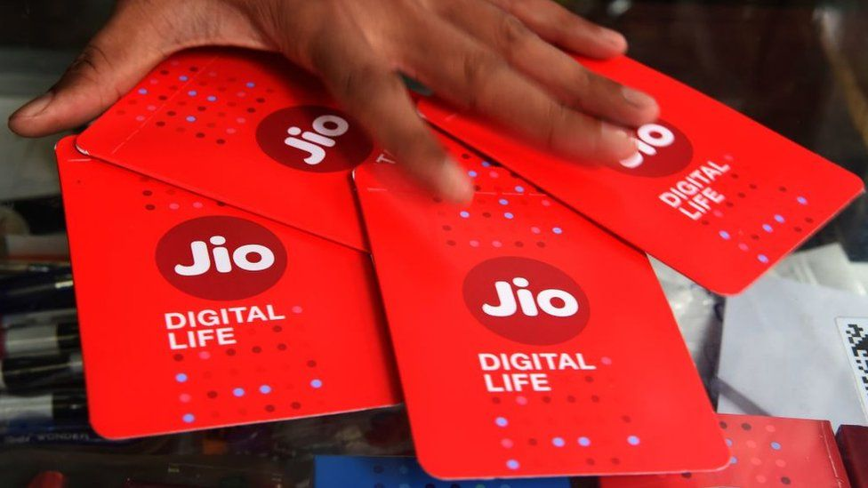 A shopkeeper collects JIO simcards at a mobile phone store in Mumbai on July 19, 2017. Indian oil-to-telecom conglomerate Reliance Industries's first-quarter consolidated profit jumped 28 percent July 20, pumped up by higher margins from its core oil refining business it said, beating analyst estimates.