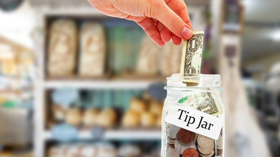 Stock photo of someone putting money into a tip jar