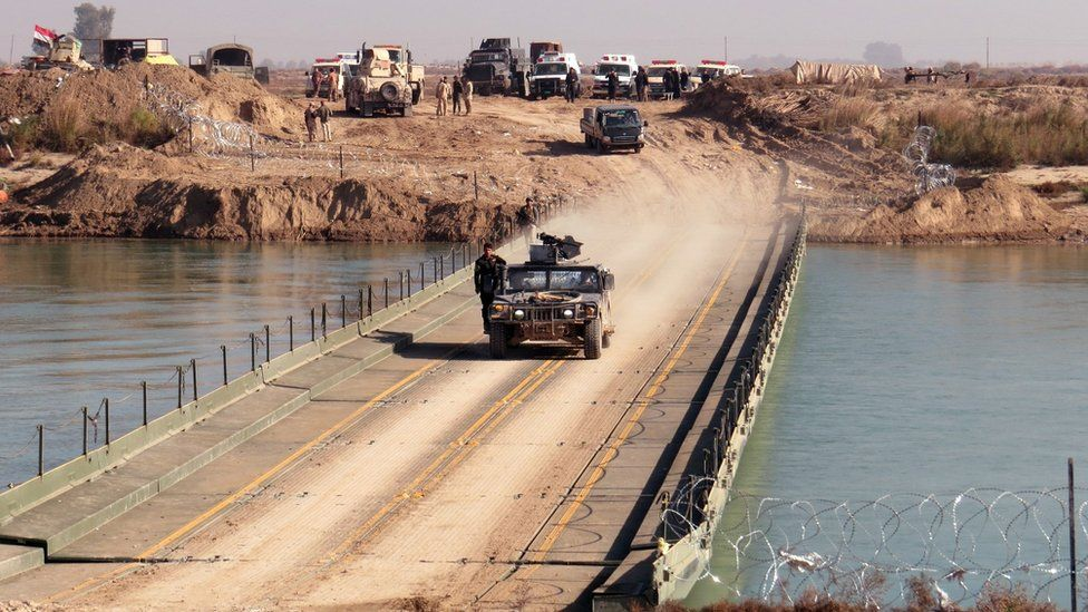 Iraqi pro-government forces cross a bridge over the Euphrates river as they take position in the al-Aramil area, south of Ramadi (22 December 2015)