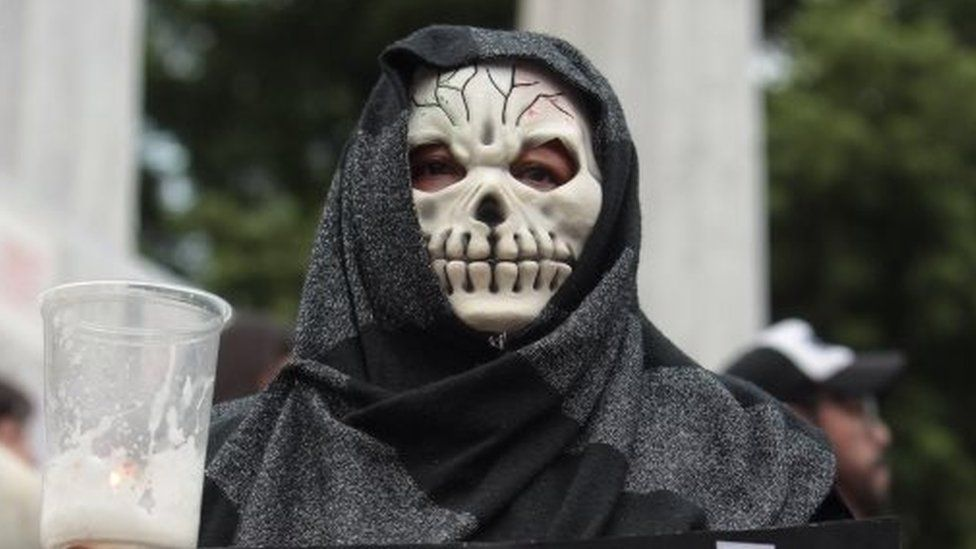 A woman wearing a skull mask takes part in a protest demanding justice in the case of the multiple homicide in which Ruben Espinosa on 8 August 2015
