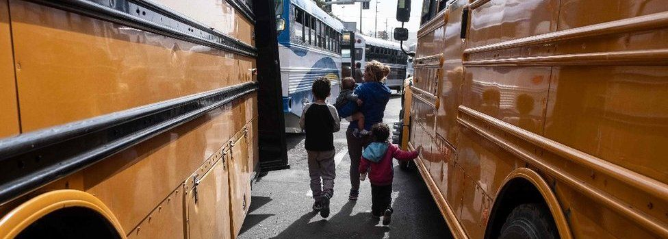 A Central American migrant woman and children walk next to buses in Tijuana, Mexico