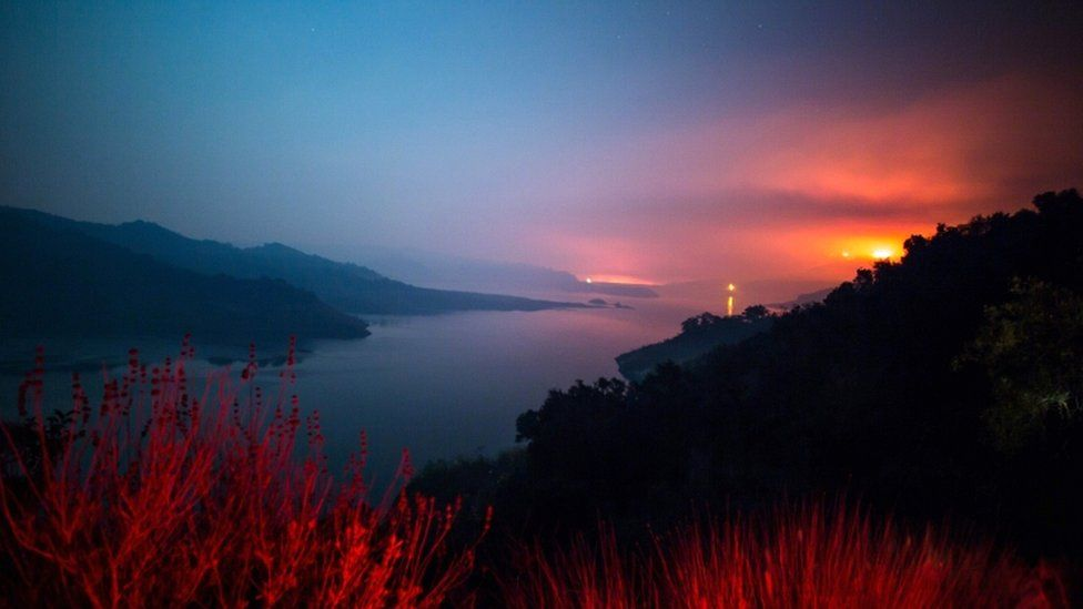 The Thomas Fire burns a hillside behind Lake Casitas in Ventura, California on 8 December 2017