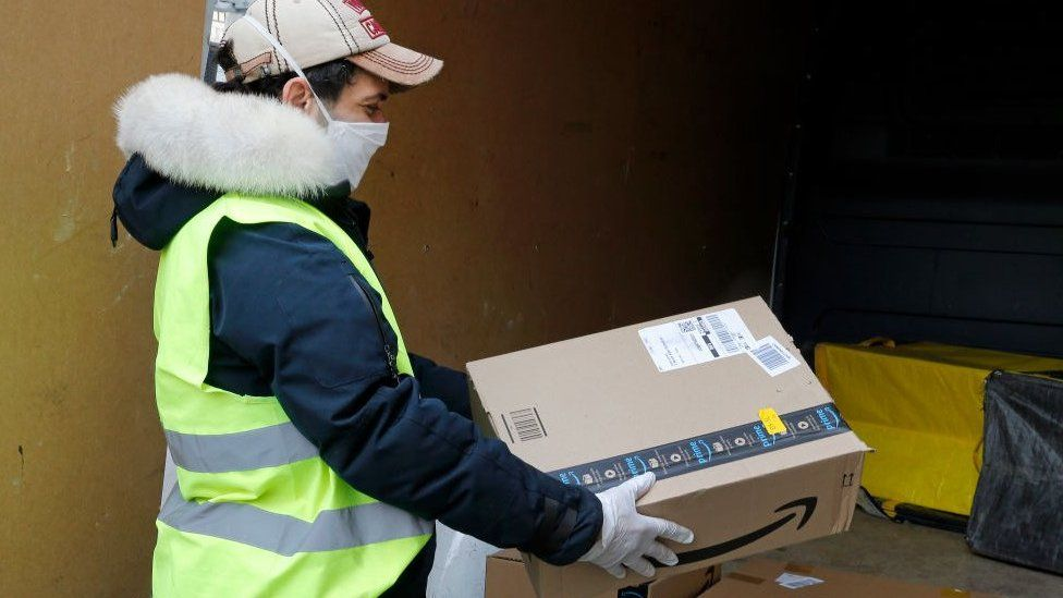 A delivery man wearing a protective mask carries an Amazon package.