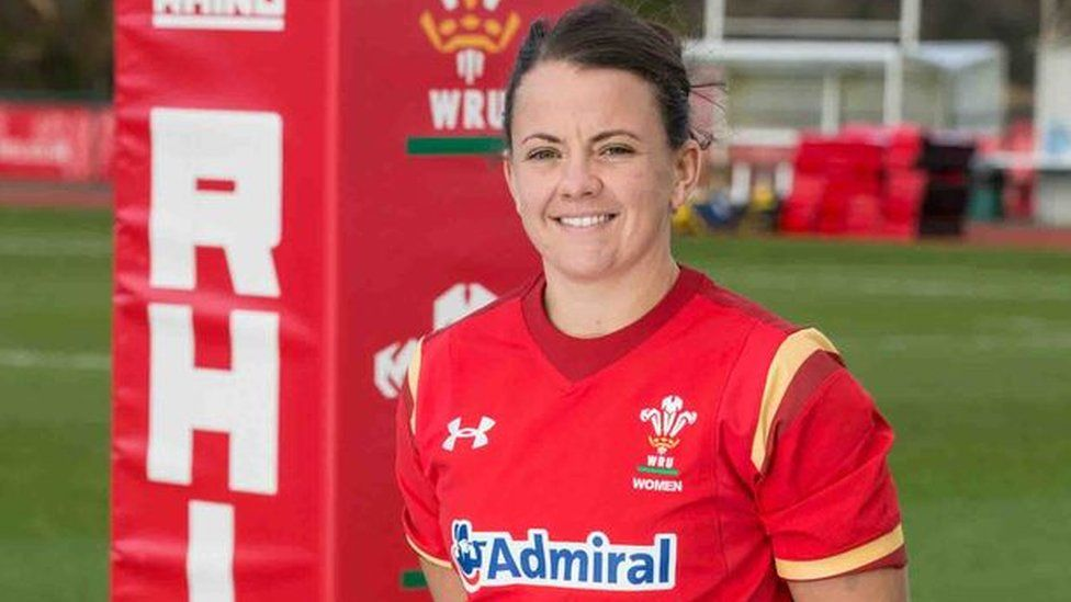 A photo of Sian Williams in Wales rugby gear, standing to attention by a padded goalpost on the field