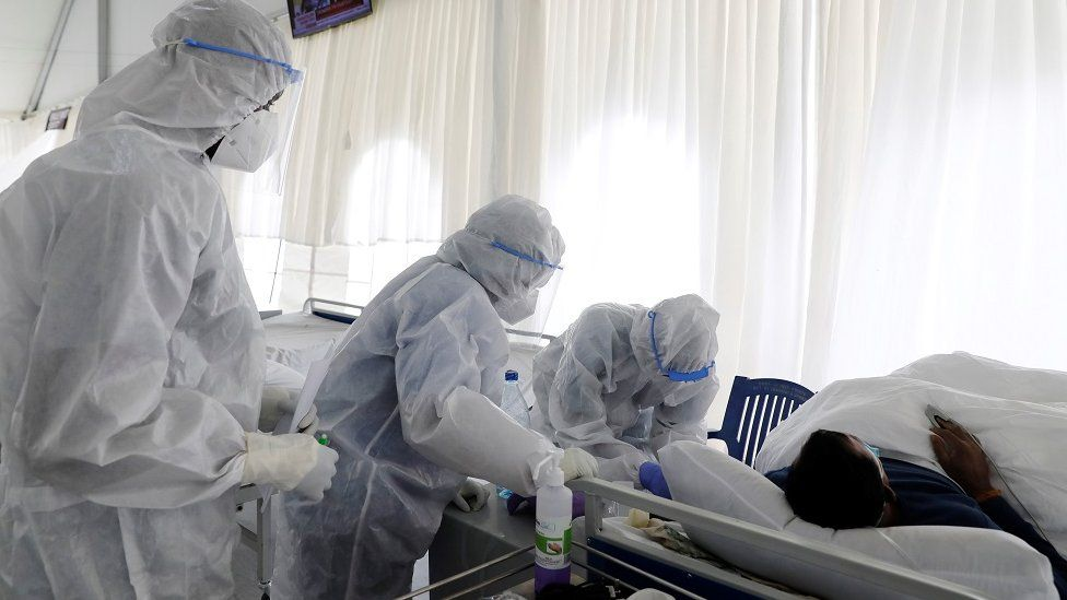 People in PPE treating a patient
