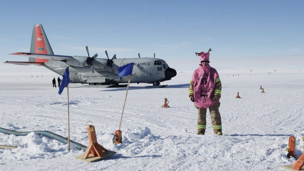 A woman in a whoopee cushion costume stands on a frozen airfield in front of a plane