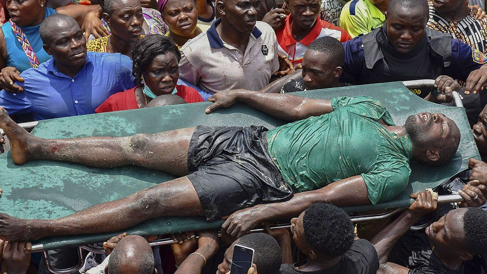 Rescue workers carry a man rescued from the ruble at the scene of a building collapse in Ita Faji, Lagos, Nigeria, 13 March 2019