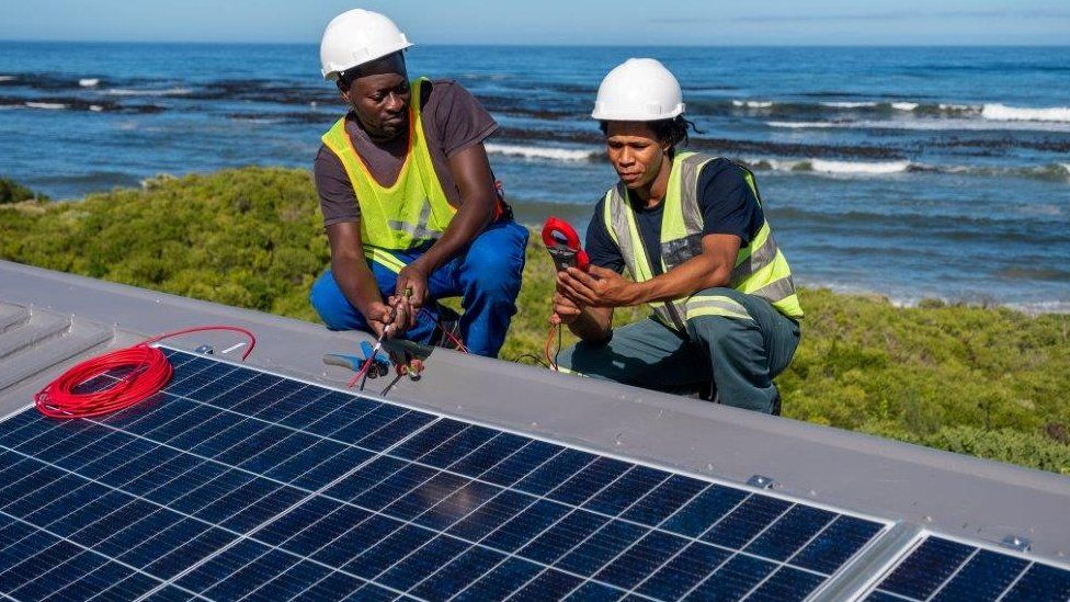 Two engineers with a solar panel