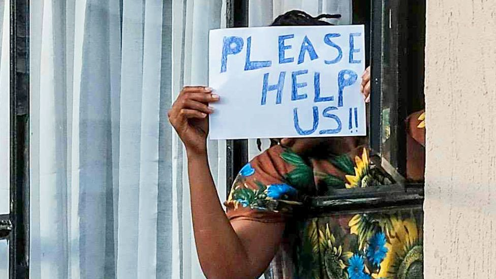 """Someone in quarantine in Kenya holding up a """"Please help us"""" sign - April 2020"""