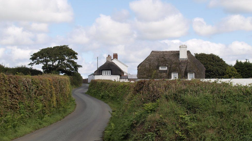 Small country road past thatched houses, Cornwall, UK