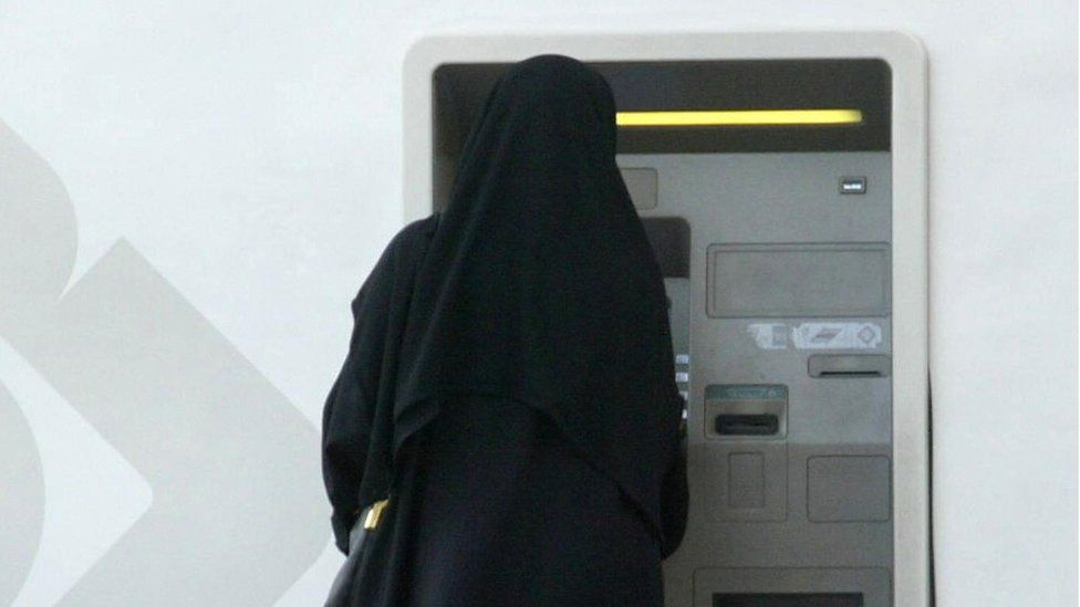 A woman in an abaya taking money out of a bank machine
