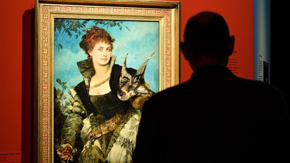 """A visitor looks at a painting entitled The Falconer by Austrian artist Hans Makart, on display in the exhibition """"Gurlitt: Status Report Nazi Art Theft and its Consequences"""" at the Art and Exhibition Hall of the Federal Republic of Germany (Bundeskunsthalle) in Bonn, Germany, 2 November 2017"""