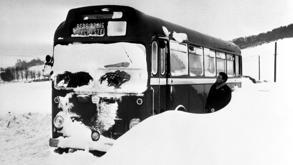 1962: With snow reaching half way up, a bus is abandoned in a snow drift on the main Poole-Dorchester road, near Briantspuddle.