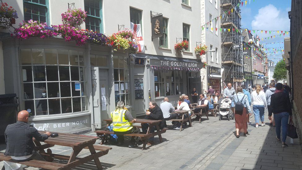 People sitting outside a pub having a drink.