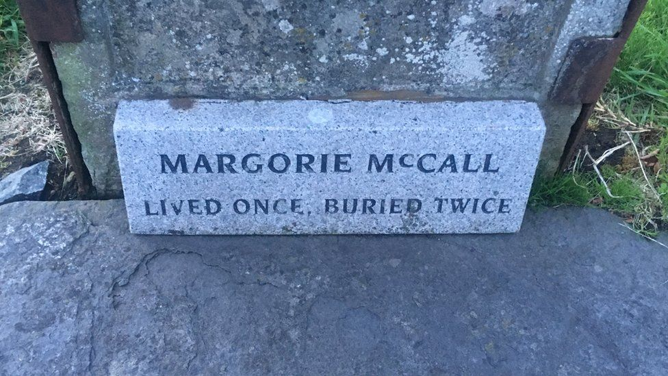 grave of Margorie McCall which says - Lived once, buried twice