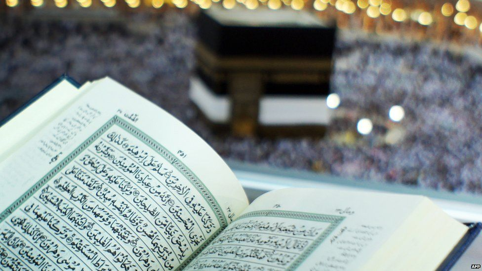 A Muslim pilgrim reads the Koran at the Great Mosque in Mecca, Saudi Arabia, with the Kaaba in the background 9 November 2010