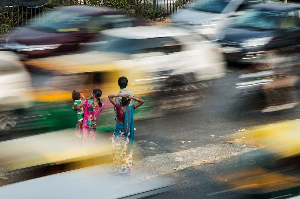 A family in New Delhi were pictured waiting for a bus during rush hour