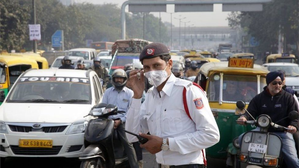 A traffic police man stands at traffic lights wearing a pollution mask during the first day of the implementation of the odd-even scheme for the vehicles in New Delhi, India, 01 January 2016.