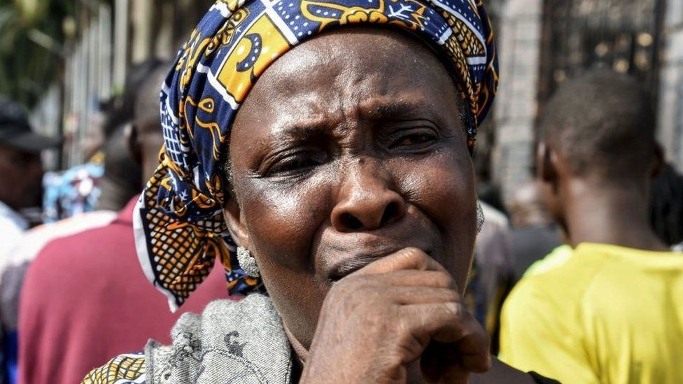 A resident cries as church members gather at the main gate of The Synagogue Church of All Nations (SCOA) headquarters to mourn the death of late Nigerian pastor TB Joshua, in the Ikotun distrcit of Lagos on June 6, 2021