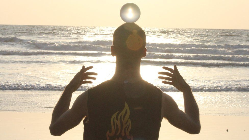 Man with crystal ball on his head