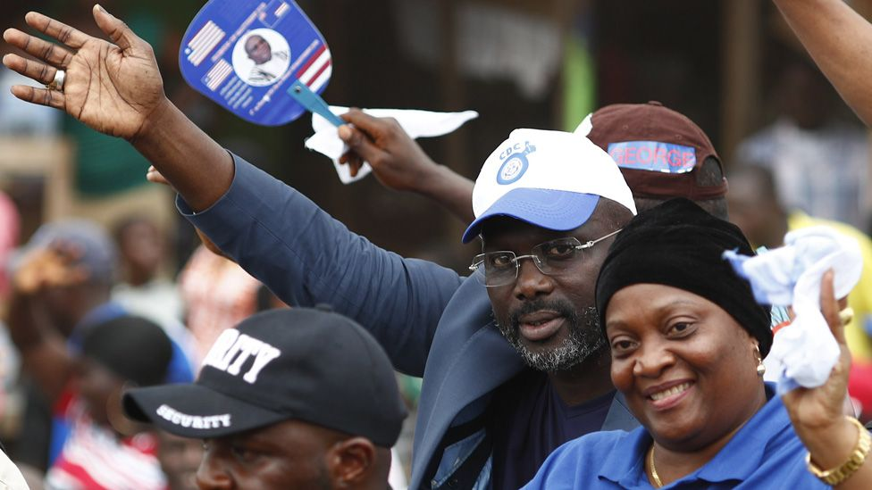 Liberian presidential candidate George Weah (C) from the Congress for Democratic Change (CDC) and running mate Jewel Howard Taylor (C-R), former wife of convicted former president Charles Taylor, wave to supporters during a campaign rally in Buchanan, Liberia, 30 September 2017.