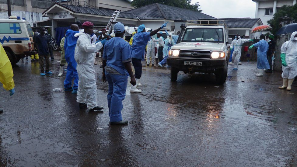 an ambulance pulls out of the mortuary with human remains that are being taken to a mass grave outside Freetown