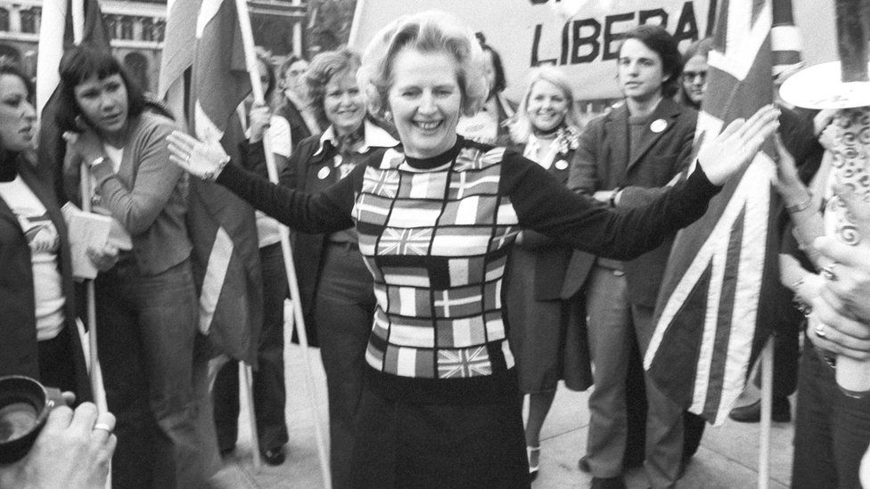 """Margaret Thatcher, sporting a sweater bearing the flags of European nations, in Parliament Square during her """"Yes to Europe"""" campaign."""