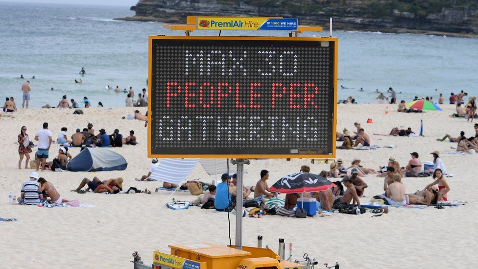 Beachgoers sit behind a sign on Bondi Beach which reads 'max 30 people per gathering'