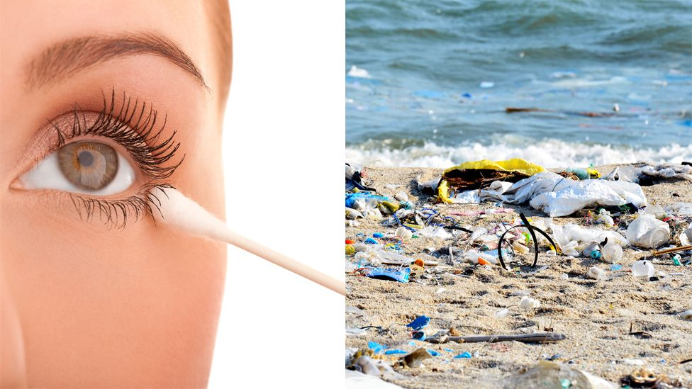A woman with a cotton bud and some plastic on a beach