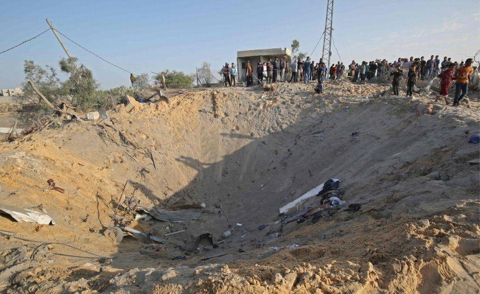 Palestinians gather around a crater after an Israeli air strike at Deir al-Balah, in Gaza