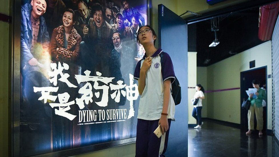 A young person in front of a 'Dying to Survive' poster