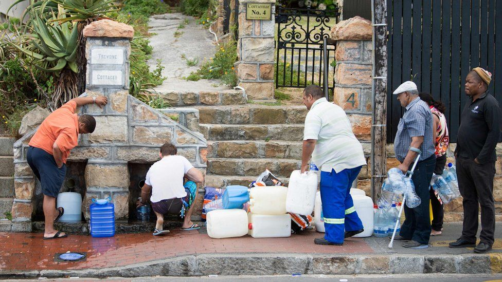 People collect drinking water from pipes fed by an underground spring, in St. James, about 25km from the city centre, on January 19, 2018, in Cape Town.