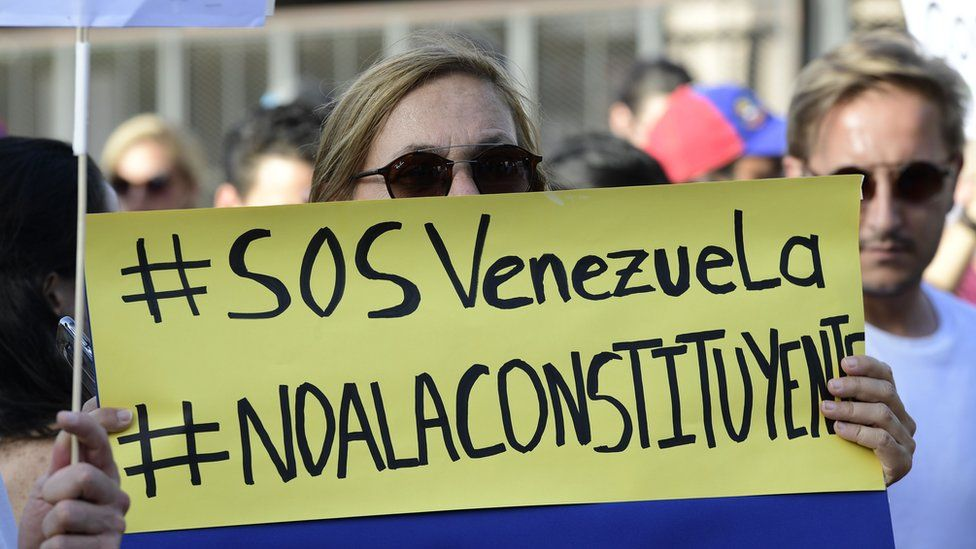 A Venezuelan holds up a placard during a protest on July 30, 2017 against Venezuelan President Nicolas Maduro and the election of a Constituent Assembly