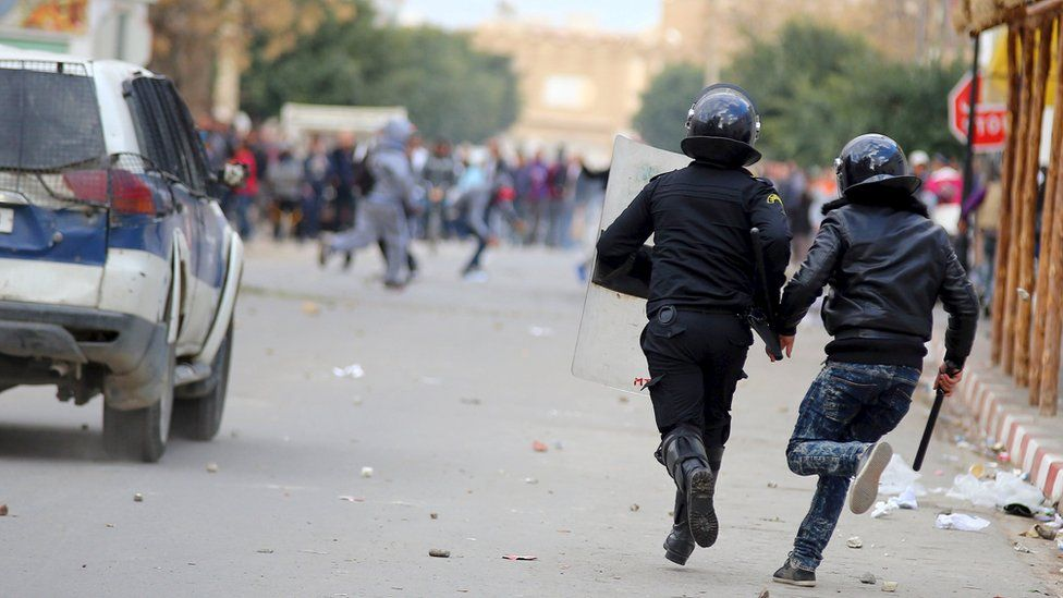 Riot policemen run after protesters during clashes in Kasserine, Tunisia January 21, 2016.