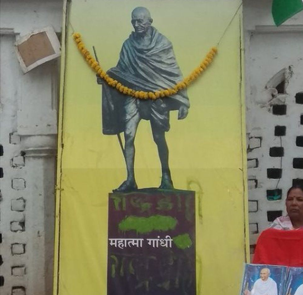 The poster with green paint on it at the memorial