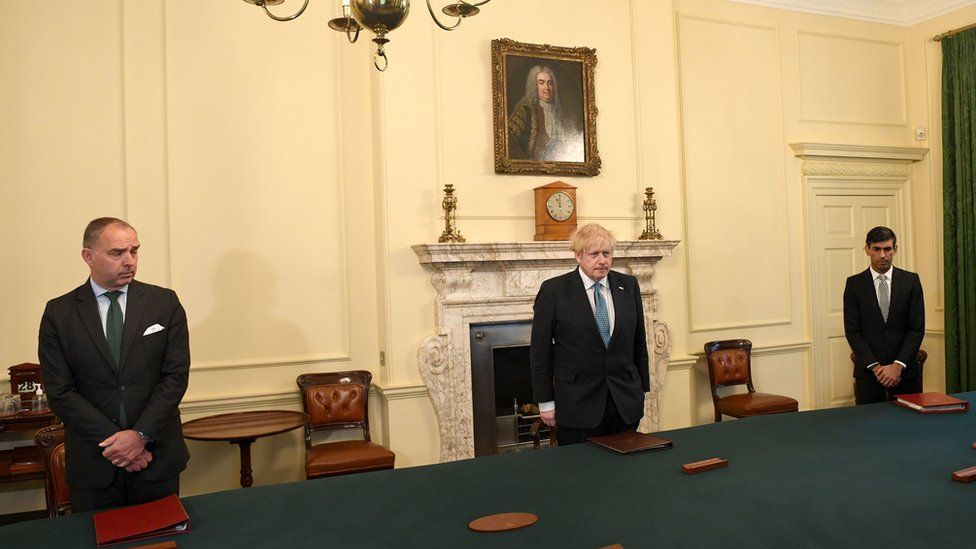 Cabinet Secretary Mark Sedwill, Prime minister Boris Johnson and Chancellor of the Exchequer Rishi Sunak stand inside 10 Downing Street, London, to observe a minutes silence in tribute to the NHS staff