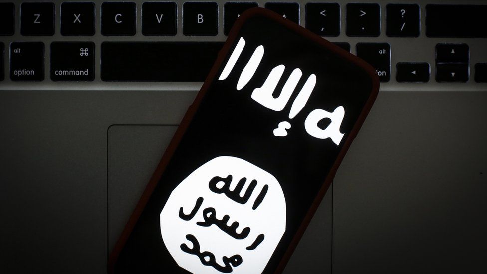 The logo of the so-called Islamic State is seen on a mobile phone