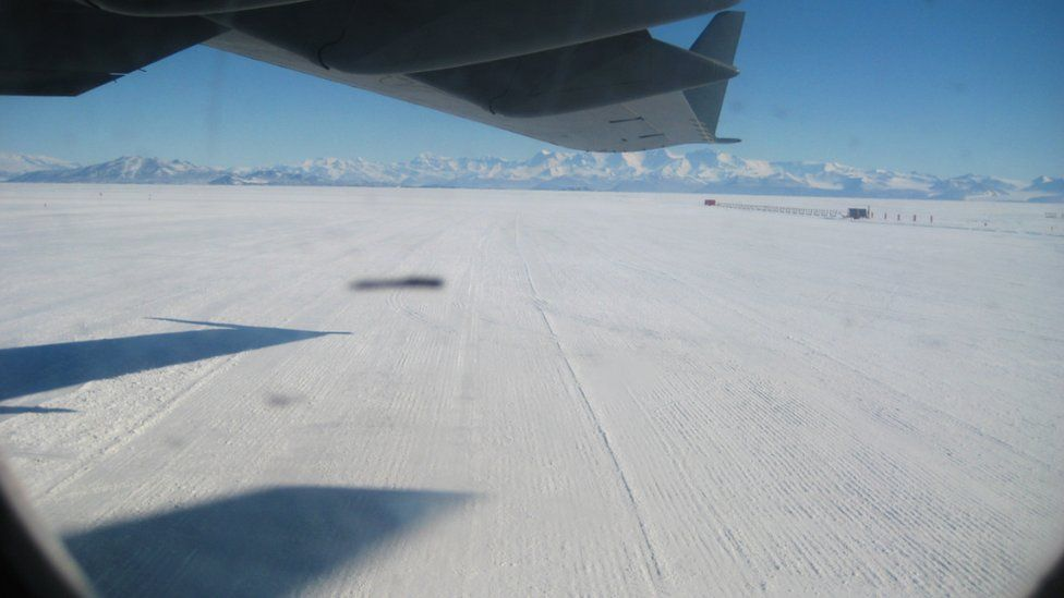 View from a plane window across a field of snow with distant mountains in the background