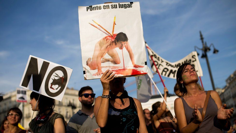 """A woman holds up a banner reading in Spanish: """"Put yourself in its place"""" as she protests with others against bullfighting in Madrid"""