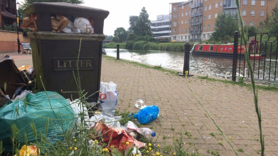 Overflowing litter bin by a canal in Northampton with bags of rubbish surrounding it.