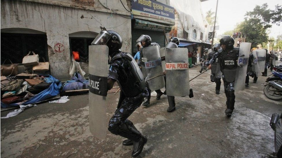 Nepalese policemen chase protesters after they burnt a copy of the new constitution during the protest organized by splinter of the Maoist party, alliance of ethnic group and Madhesi party, in Kathmandu, Nepal, Monday, Sept. 21,2015