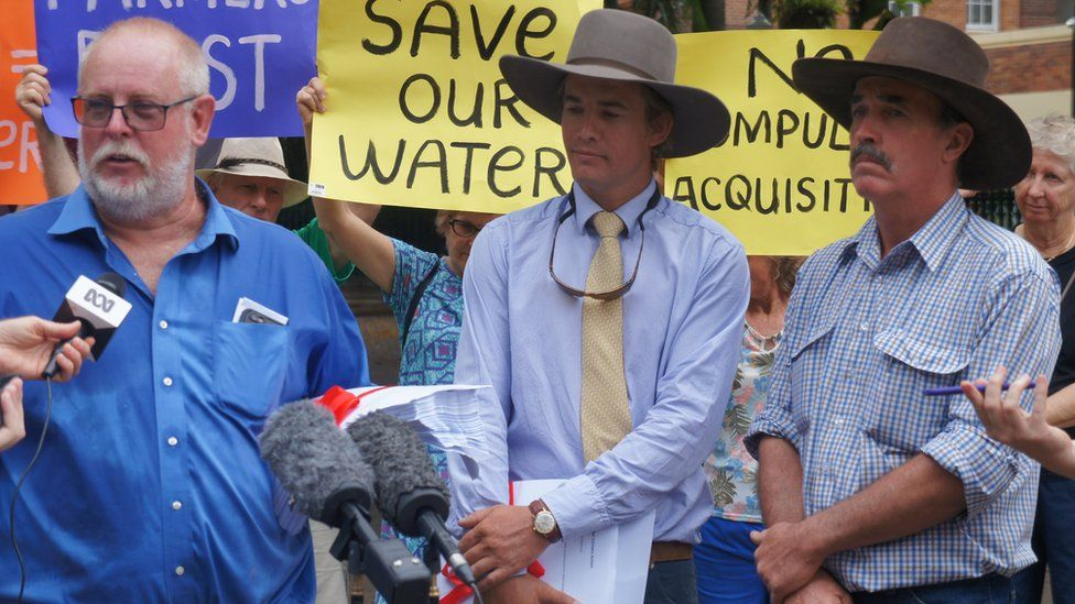 Three farmers at a protest with a placard behind them reading 'save our water'