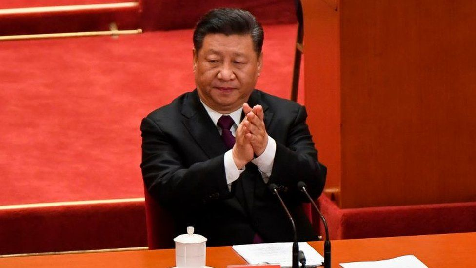 China's President Xi Jinping applauds during a celebration meeting